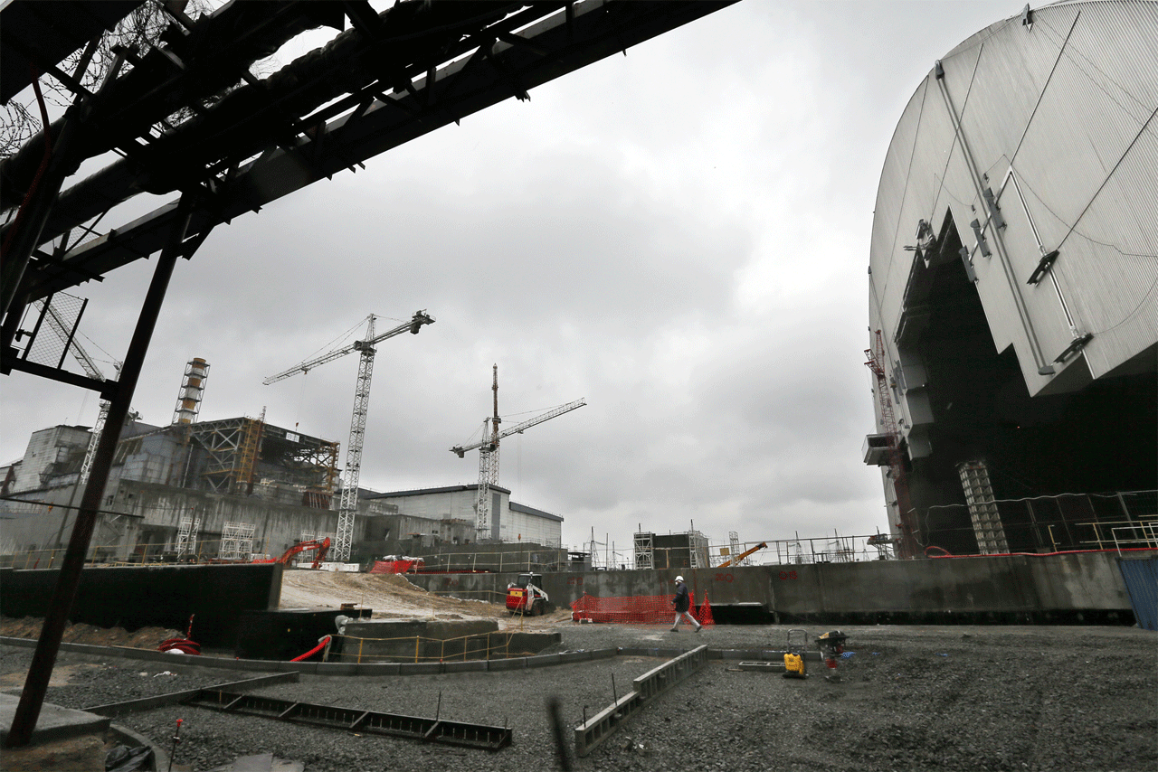 4号機(左)とアーチ型シェルター(右)の間でレールを建設中。年内にもシェルターの移動を開始する計画